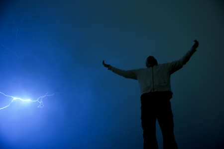worshipping: Man with outstretched arms in lightning storm