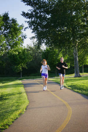 Man and woman jogging on trail photo