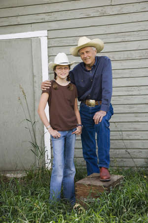 Grandfather and granddaughter wearing cowboy hats photo