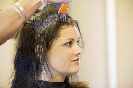 Woman having her hair dyed Imagens