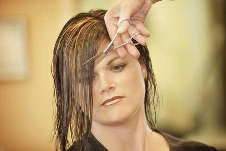 Vrouw met haar haren knippen  Stockfoto
