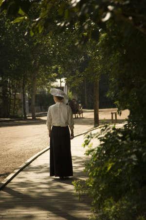 old people: Old-fashioned woman walking down board-walk street Stock Photo