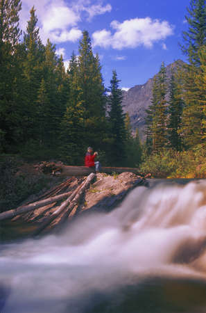 Person drinking coffee beside a waterfall photo
