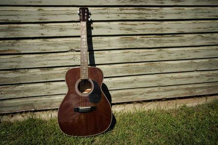 アコースティック ギターの建物にもたれて