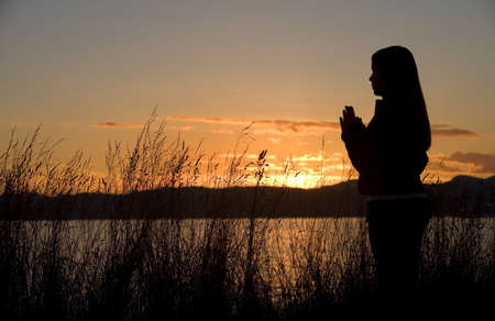 A teenage girl prays at sunset by the ocean.