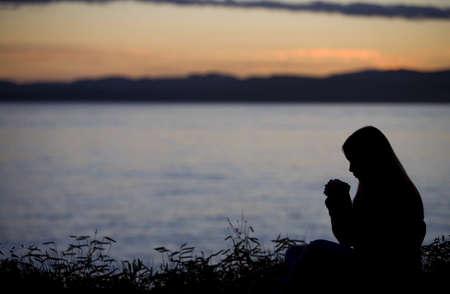 A teenage girl praying over lake photo