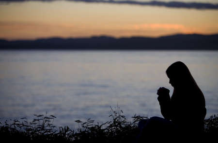 belief systems: A teenage girl praying over lake