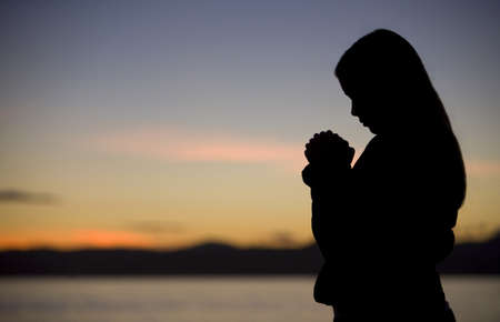 A teenage girl prays at sunset by the ocean. photo