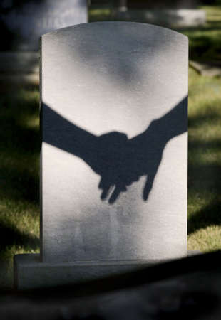 grave site: Shadow on tombstone of two clasped hands