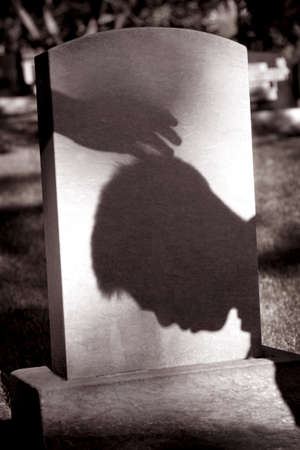 shadow: Shadow of hand over head of grieving man at grave site