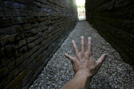 enclosed: Hand reaching down narrow alley towards light