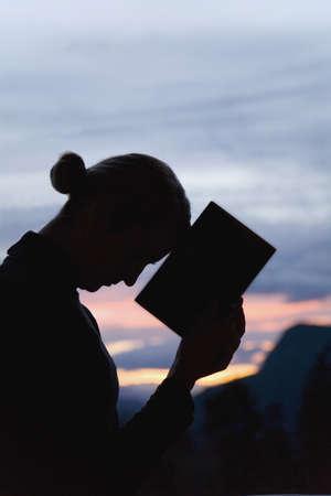 mujeres orando: Silueta de mujer con un libro  Foto de archivo
