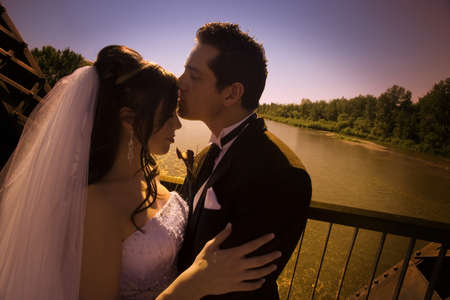 Groom kissing bride photo