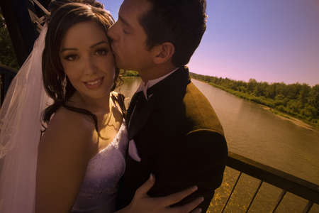 Groom kissing bride photo