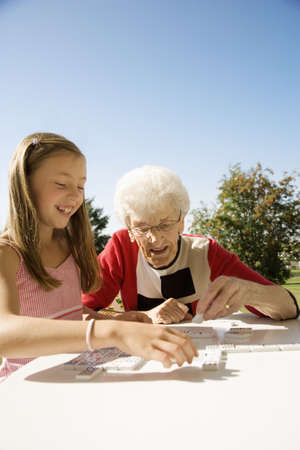 domino: Grandmother and granddaughter playing a game