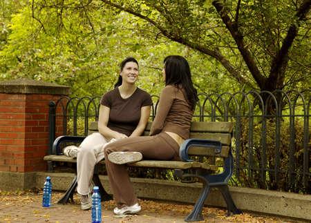 personas tomando agua: Dos mujeres, sentado en el banquillo del Parque  Foto de archivo