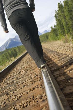 careless: Woman walking on train tracks Stock Photo