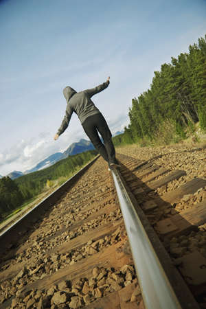 balance concept: Woman walking on railroad track