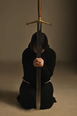 humility: Person kneeling with a sword Stock Photo