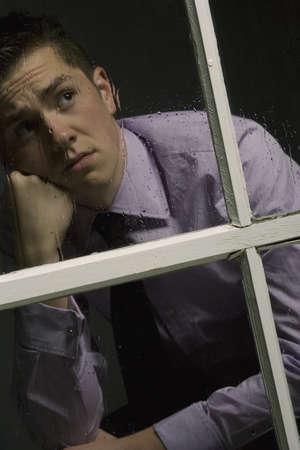 lloviendo: Hombre infeliz mirando una ventana  Foto de archivo