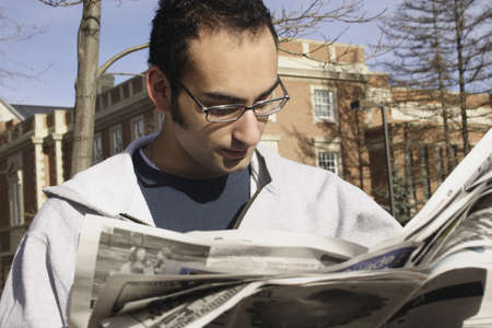 inform information: Young man reading newspaper outside