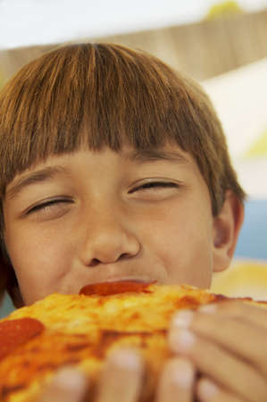 Boy eating a piece of pizza photo