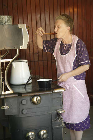 stove: A woman sampling food  Stock Photo
