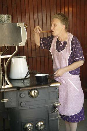 estufa: Un alimento de muestreo de la mujer  Foto de archivo
