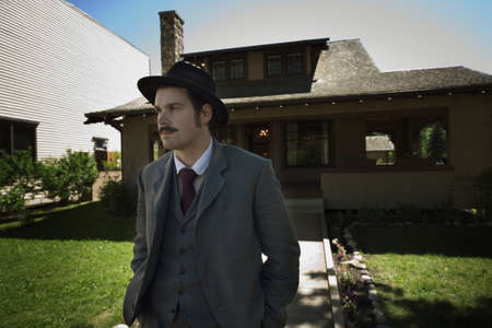Man in vintage clothing outside of house