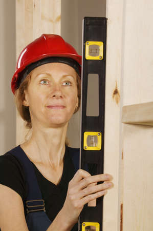 fortysomething: Female construction worker using a level Stock Photo