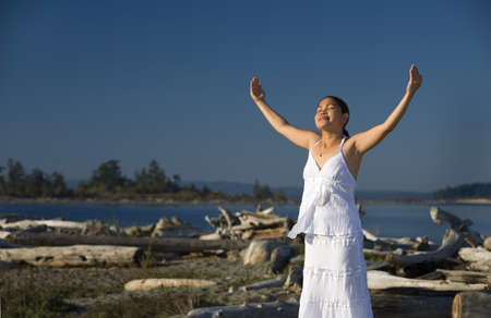 intercessor: A young woman with arms raised on the beach Stock Photo