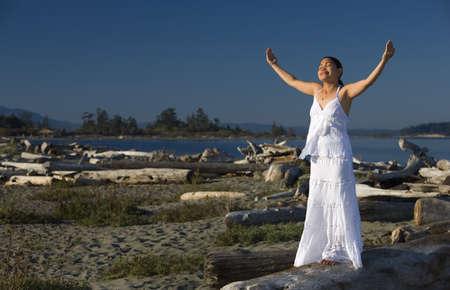 Woman praying at the beach photo