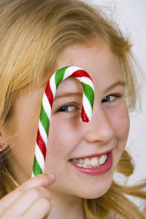 Young girl holding a candy cane photo