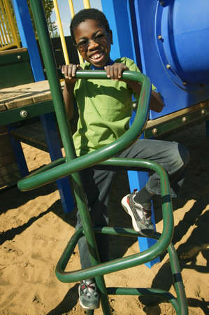 A young boy climbing on playground equipment