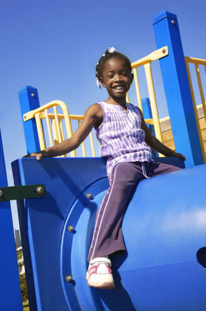children at play: Little girl sitting atop playground equipment