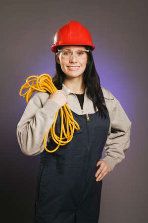 tradeswomen: Tradeswoman in coveralls, holding an extension cord