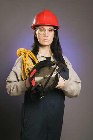 tradeswomen: Tradeswoman holding an extension cord and a power saw