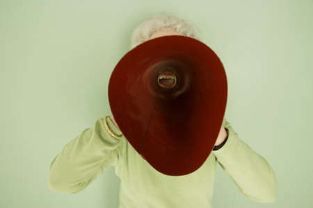 seventy something: Woman shouting into a bullhorn Stock Photo