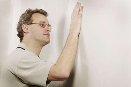 smoothness: Man checking the smoothness of a wall Stock Photo