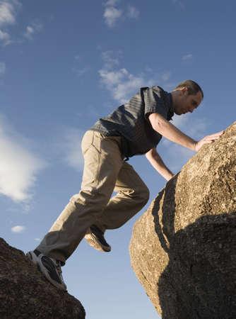 raniszewski: Man climbing up rocks Stock Photo