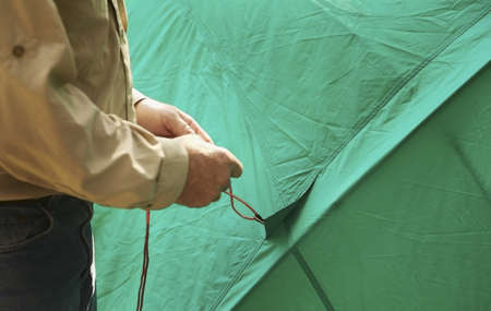 bodypart: Man holding the rope to a tent Stock Photo