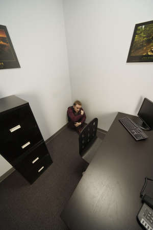 frightfulness: Man hiding in office corner
