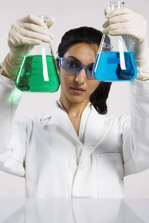 Woman holding two beakers up photo