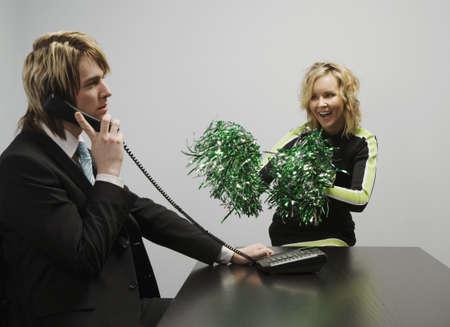 pompom: Imprenditore Il telefono accanto Cheerleader Archivio Fotografico