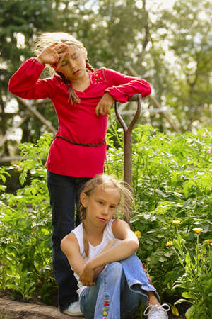 cooperating: Two girls resting from garden work Stock Photo