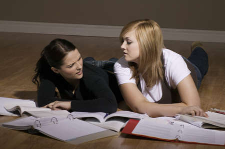 Two women studying on the floor Stock Photo