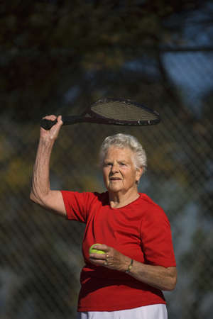 seventy something: Woman ready to serve tennis ball