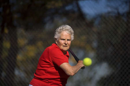 60 years old: Woman ready to hit tennis ball