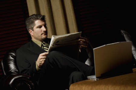 fortysomething: Businessman reading the paper with his laptop
