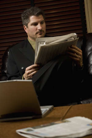 fortysomething: Businessman reading the newspaper with laptop Stock Photo